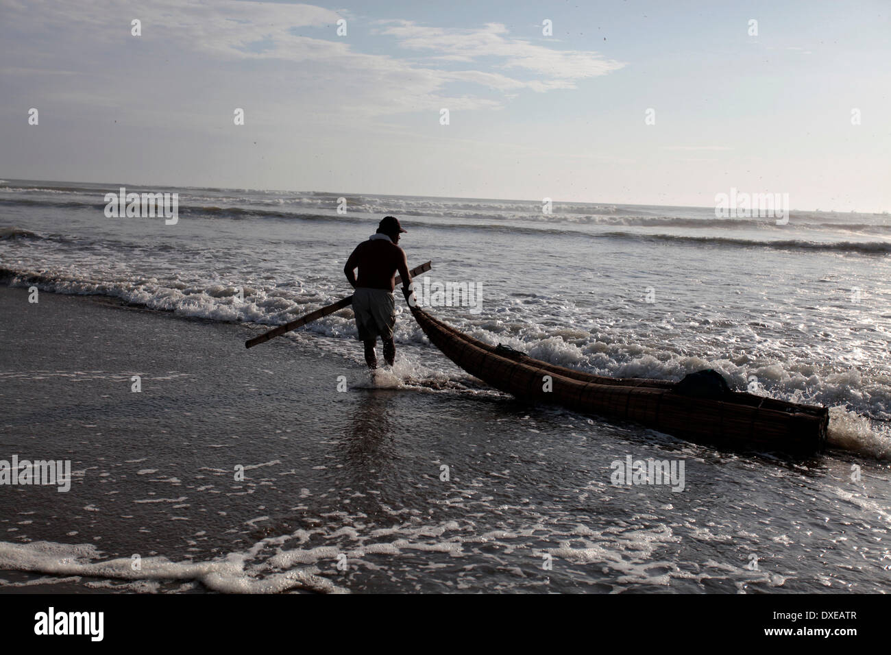 PIMENTEL, PERU - MARCH 22: Luis a fisherman in 'Totora Horses' is seen on the beach of Pimentel preparing his departure to start your fishing trip in Pacific Ocean, about 800 kilometers north of Lima in Pimentel, Peru, Saturday, March 22, 2014. Luis is 35 years in the art of fishing, live around with his wife and children, who supports with money from direct sales of products fresh from the sea. The 'Totora Horses' are Built with cattail rushes like the ethnic group of the Inca empire Mochica already made five centuries ago. The canoes are used daily to go deep into the ocean, to return after  - Stock Image