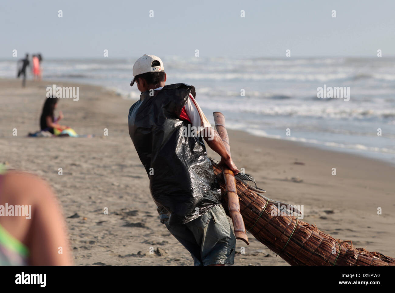 PIMENTEL, PERU - MARCH 22: Mario a fisherman in 'Totora Horses' is seen arriving at the beach  of Pimentel after a day of fishing in Pacific Ocean, about 800 kilometers north of Lima in Pimentel, Peru, Saturday, March 22, 2014. The 'Totora Horses' are Built with cattail rushes like the ethnic group of the Inca empire Mochica already made five centuries ago. The canoes are used daily to go deep into the ocean, to return after working for Between 8 and 12 hours with 50 kg of fish trapped with nets. Today fishing tends to decrease and thus the income of fisherfolk. Photo by Elkin Cabarcas - Stock Image