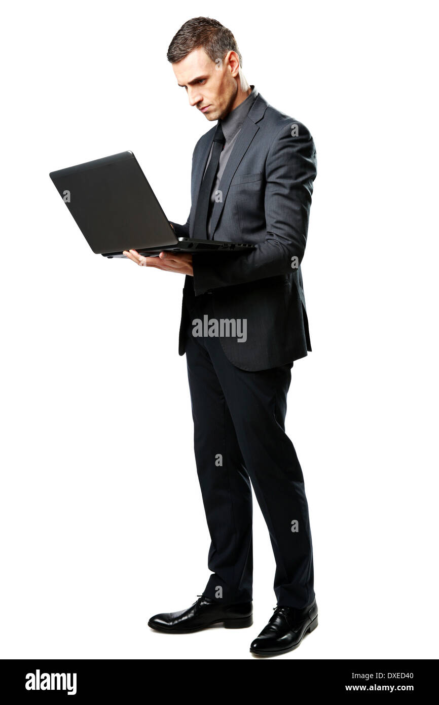Full-length portrait of a businessman standing and using laptop isolated on a white background - Stock Image