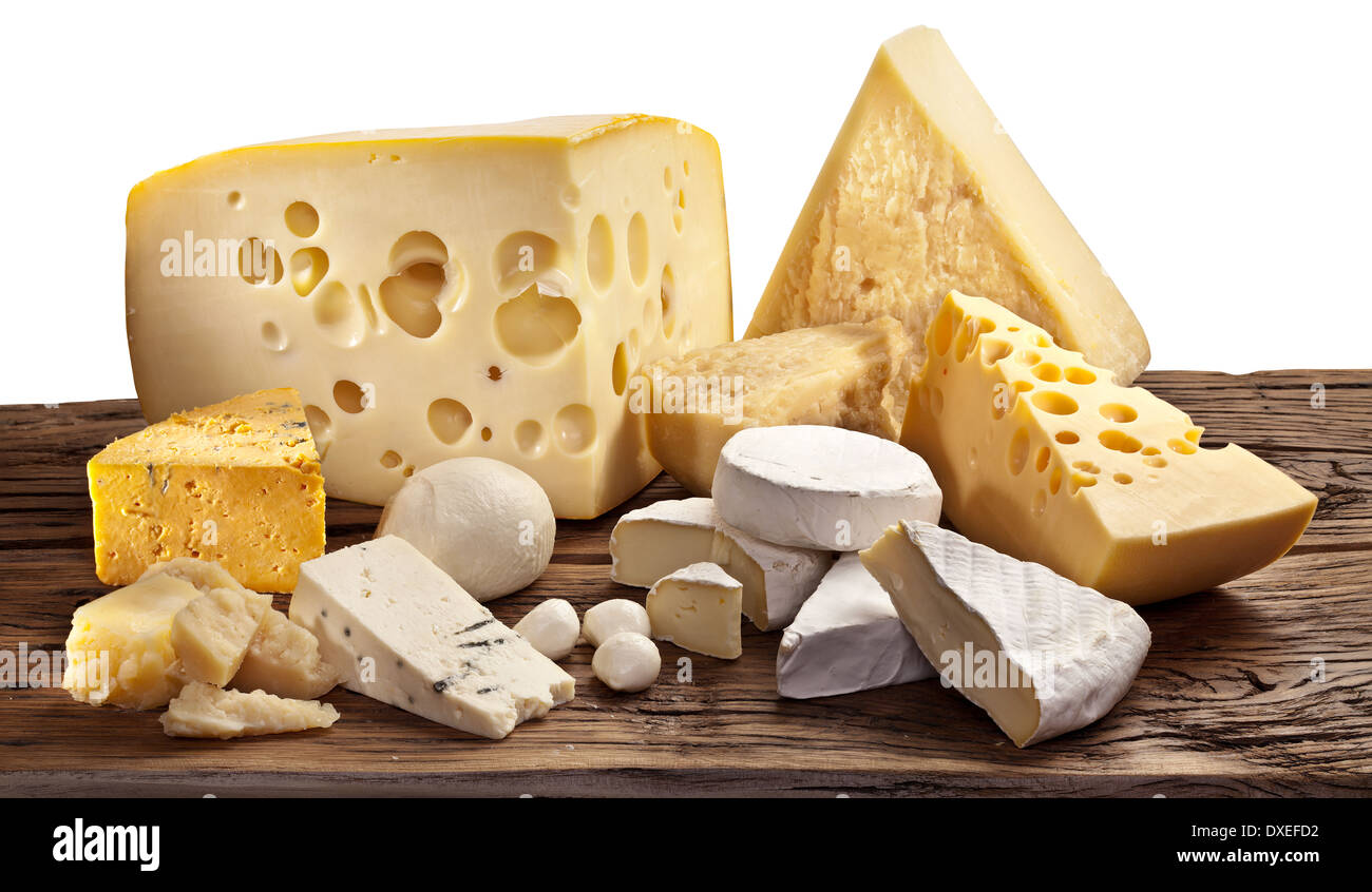 Different types of cheese over old wooden table.File contains clipping paths. - Stock Image