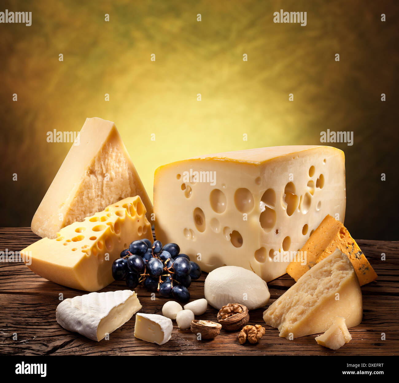 Different types of cheese over old wooden table. - Stock Image
