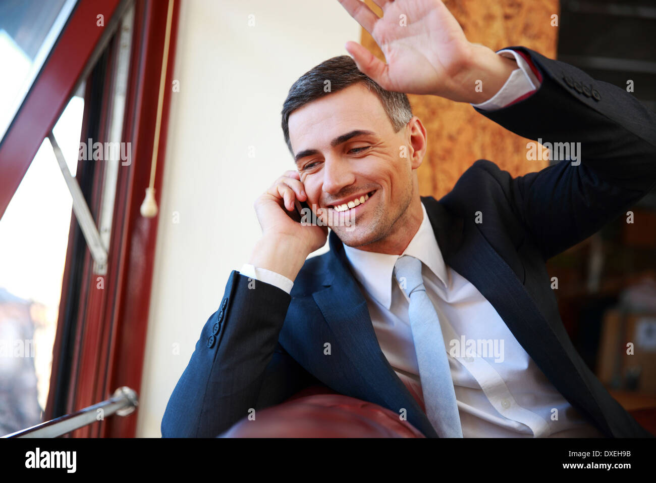 Happy businessman talking on the phone and looking in window at office - Stock Image