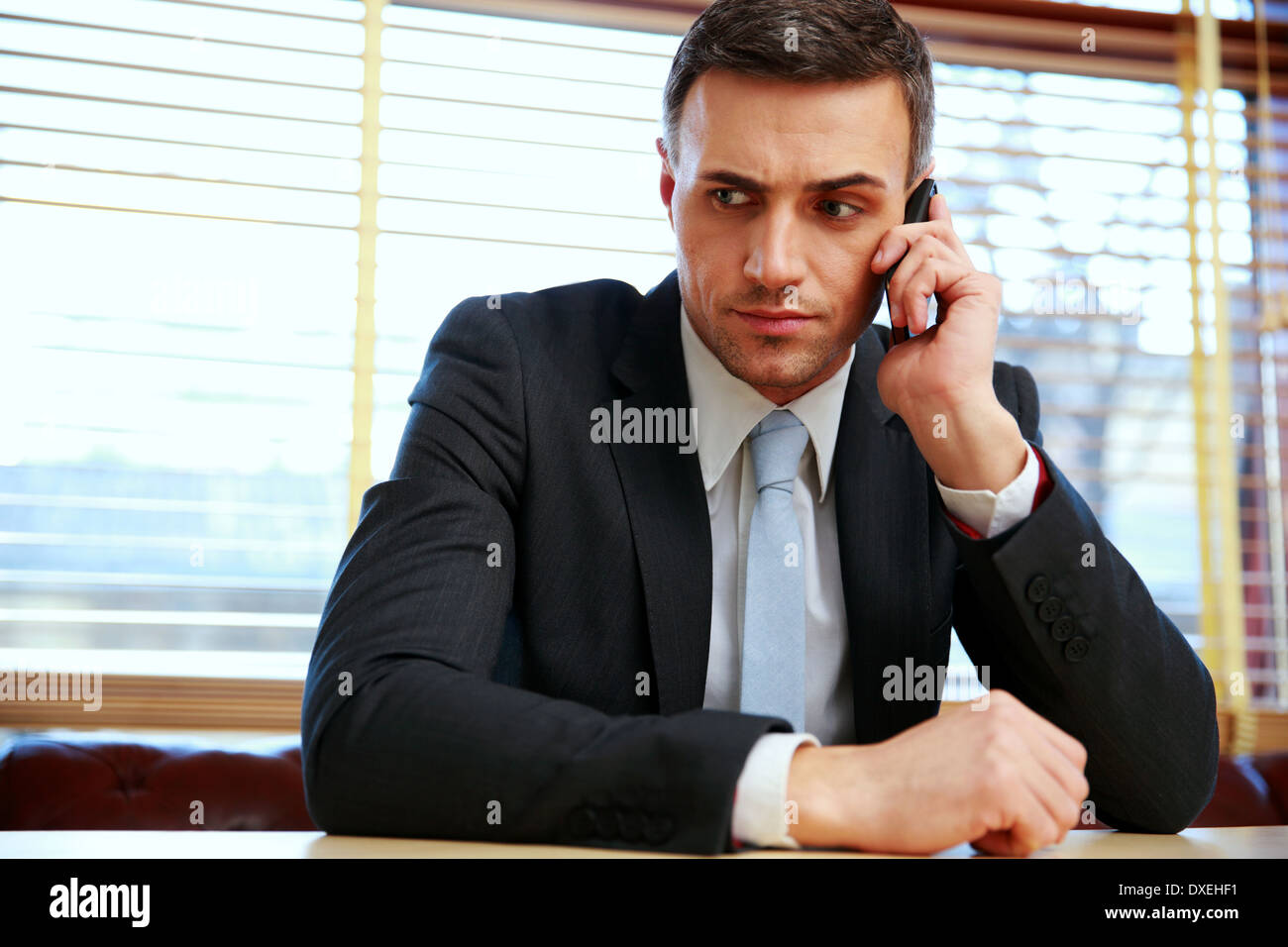 Pensive businessman sitting and talking on the phone at office - Stock Image
