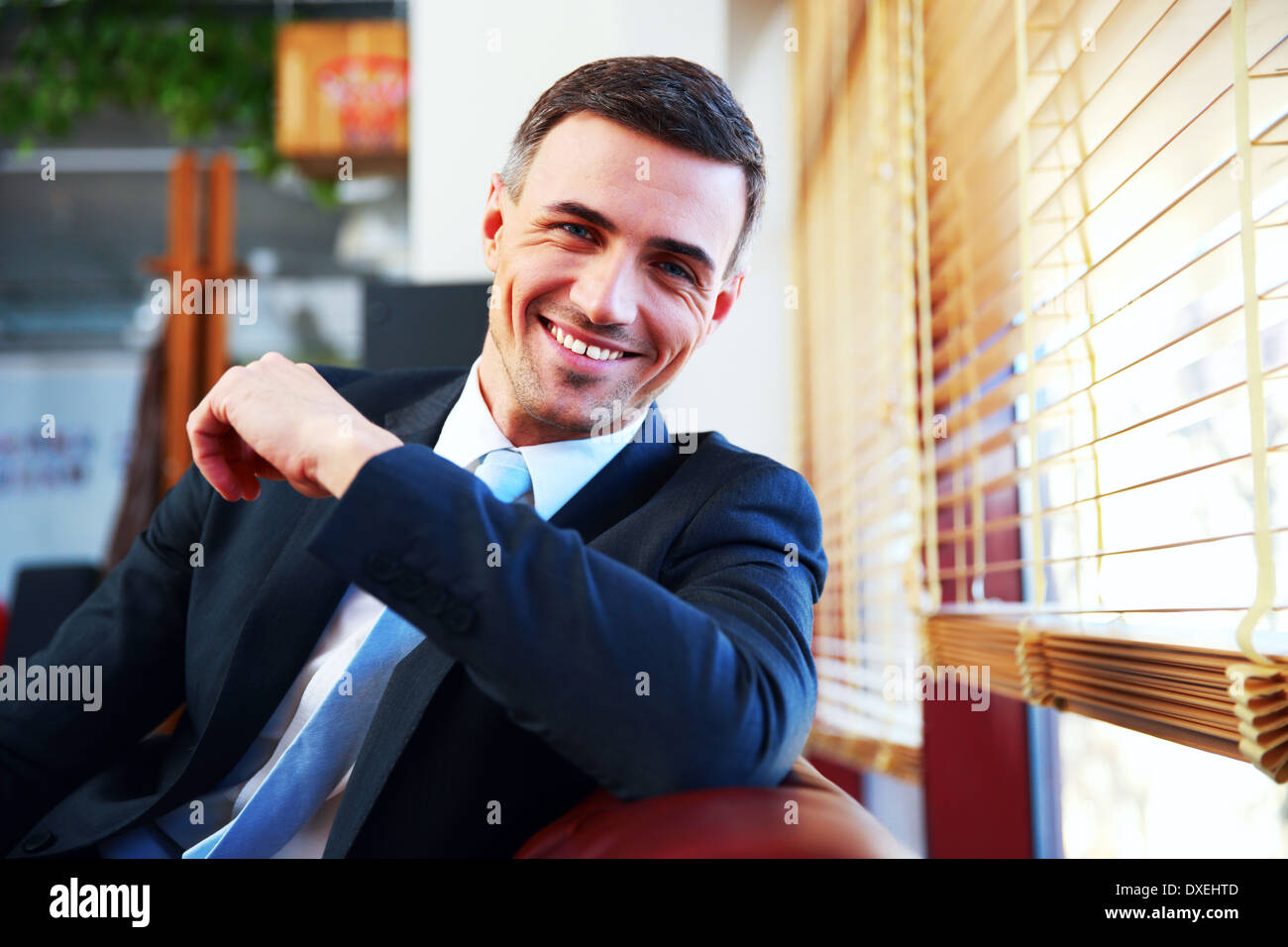 Portrait of a handsome happy businessman in suit - Stock Image