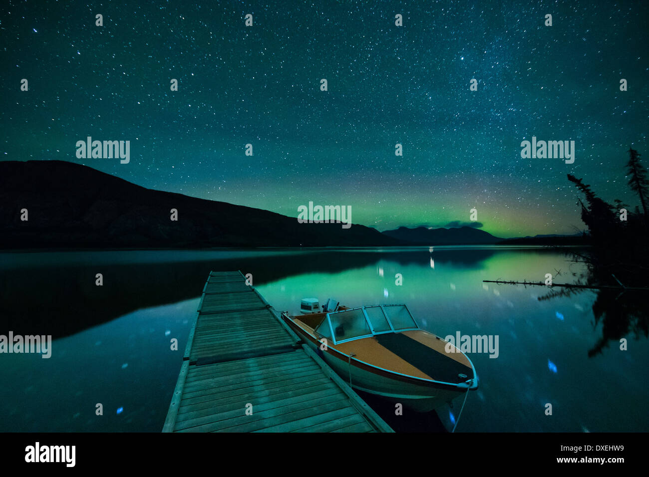 The Aurora Borealis (Northern Lights) over Ruby Mountain and Pine Lake. Yukon Territories, Canada - Stock Image
