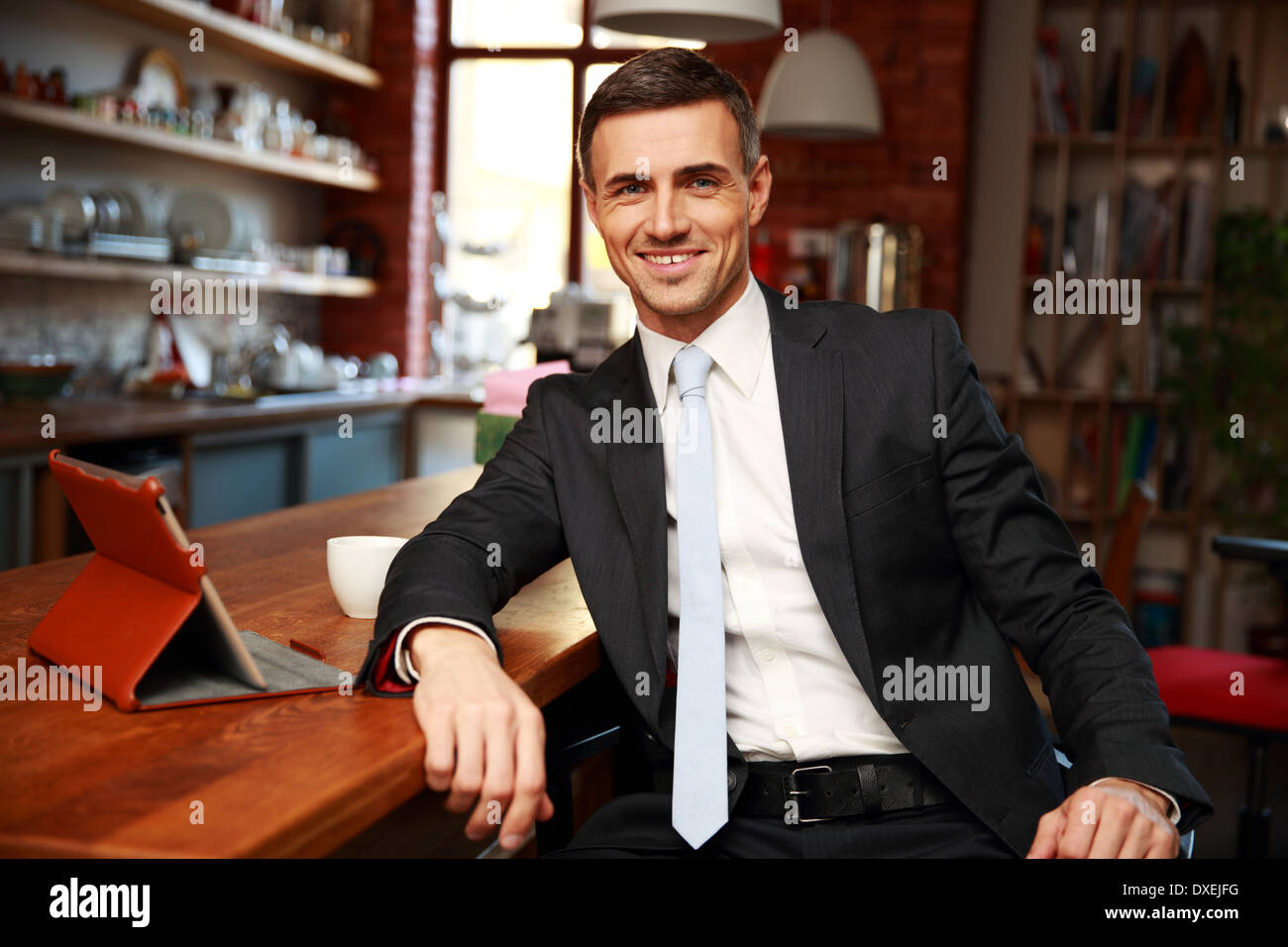 Happy businessman in formal cloths drinking coffee and reading news in the kitchen - Stock Image