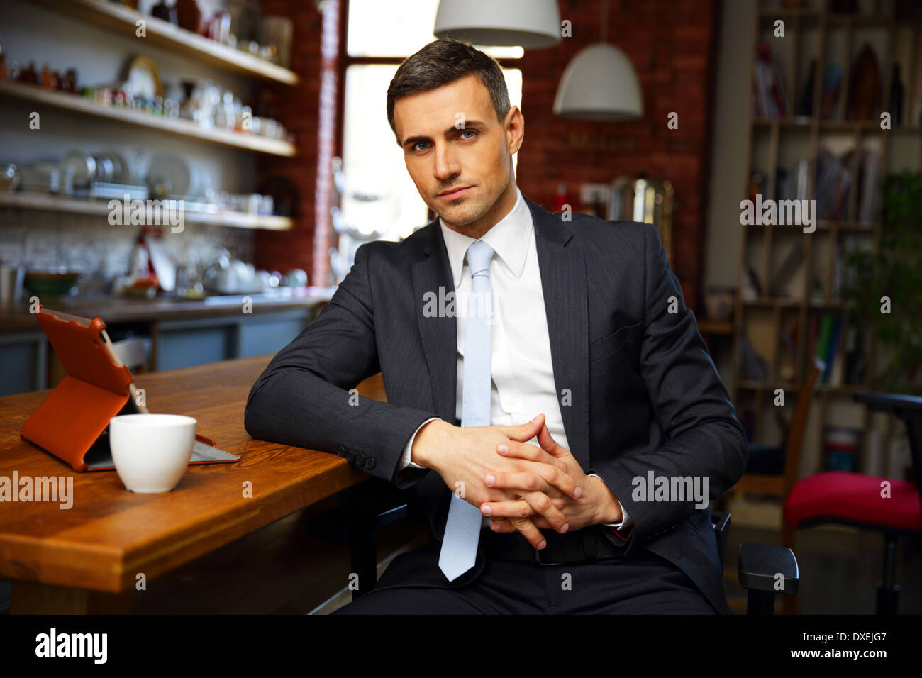 Confident businessman in formal cloths drinking coffee and reading news in the kitchen - Stock Image