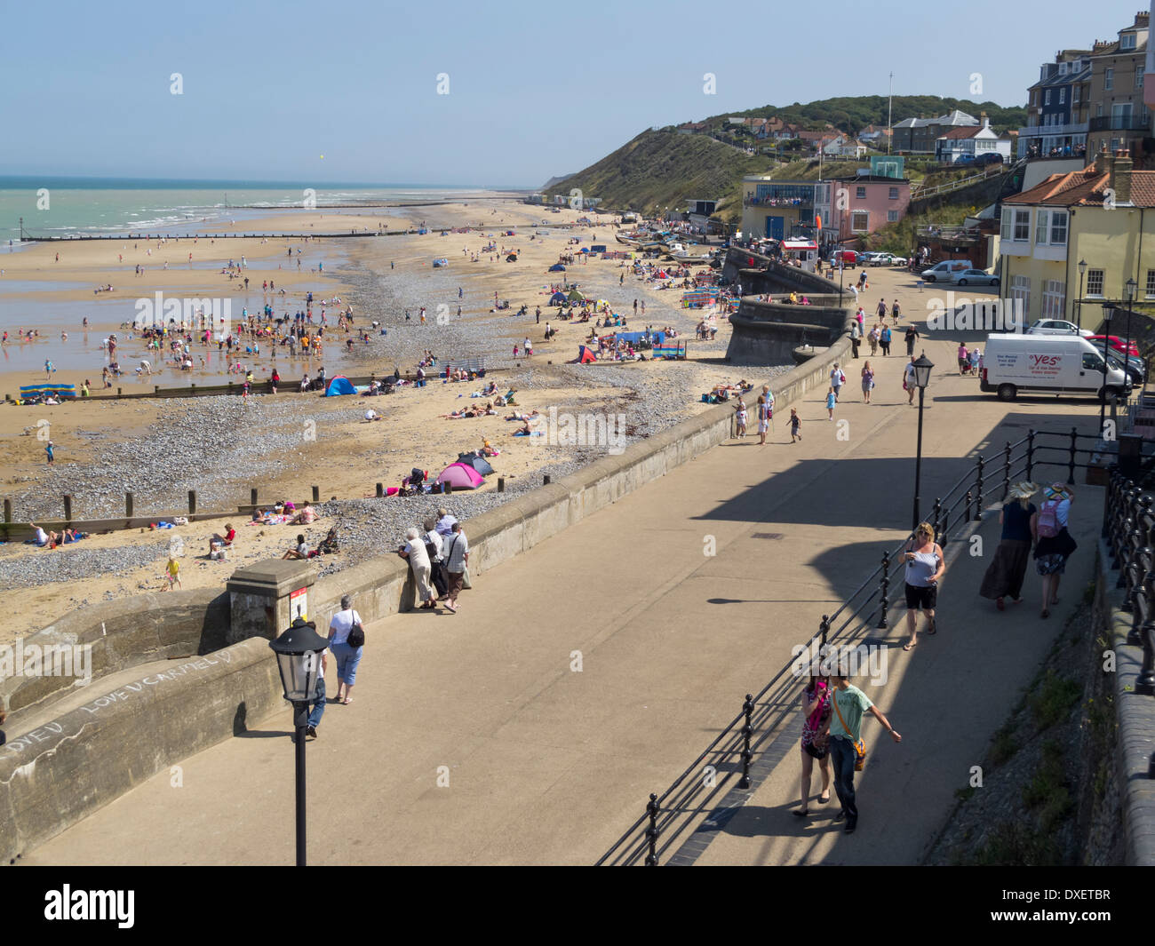 Cromer seafront and promenade with crowds of holidaymakers on the beach Norfolk East Anglia England - Stock Image