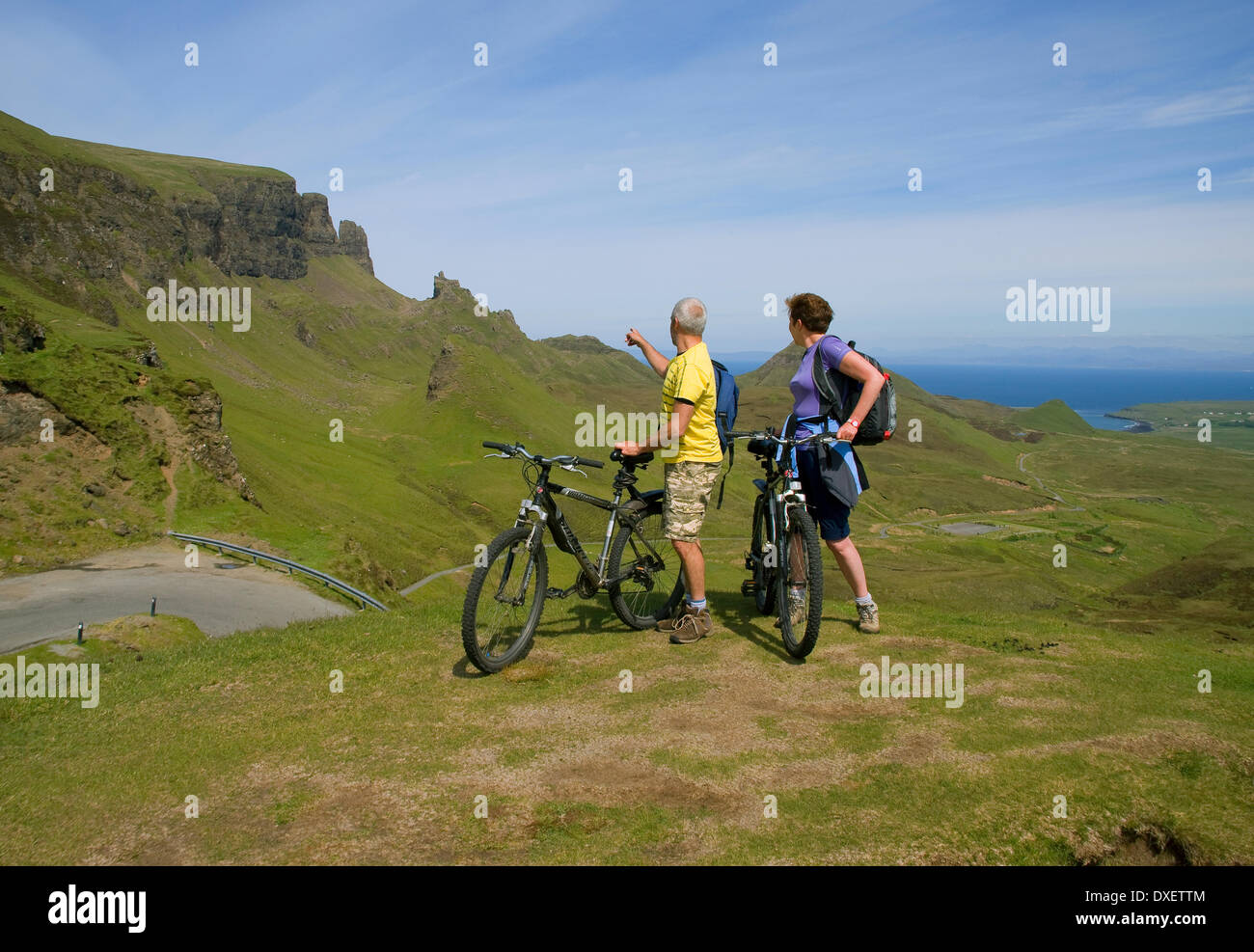 Cyclists pause to take in the magnificent view at the Quiraing pass, Isle of Skye. - Stock Image