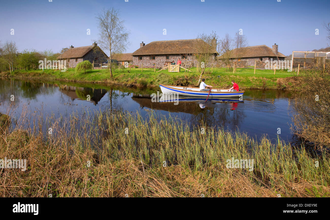 Rowing boat with thatched cottages on Loch Nell Argyll - Stock Image