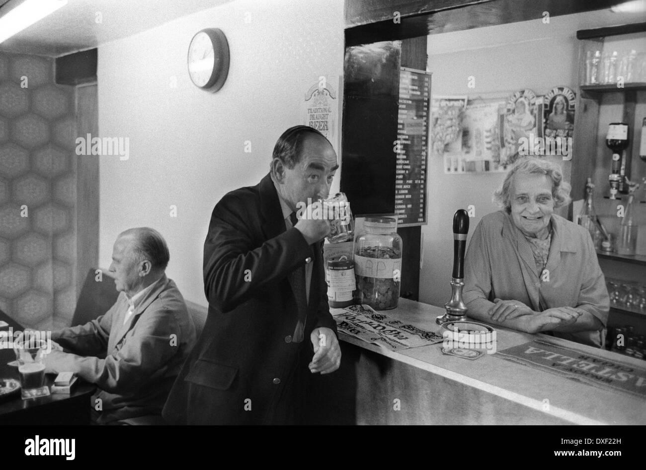 Pub interior 1970s Shropshire village life Landlady and customer at the bar. England 70s UK HOMER SYKES - Stock Image