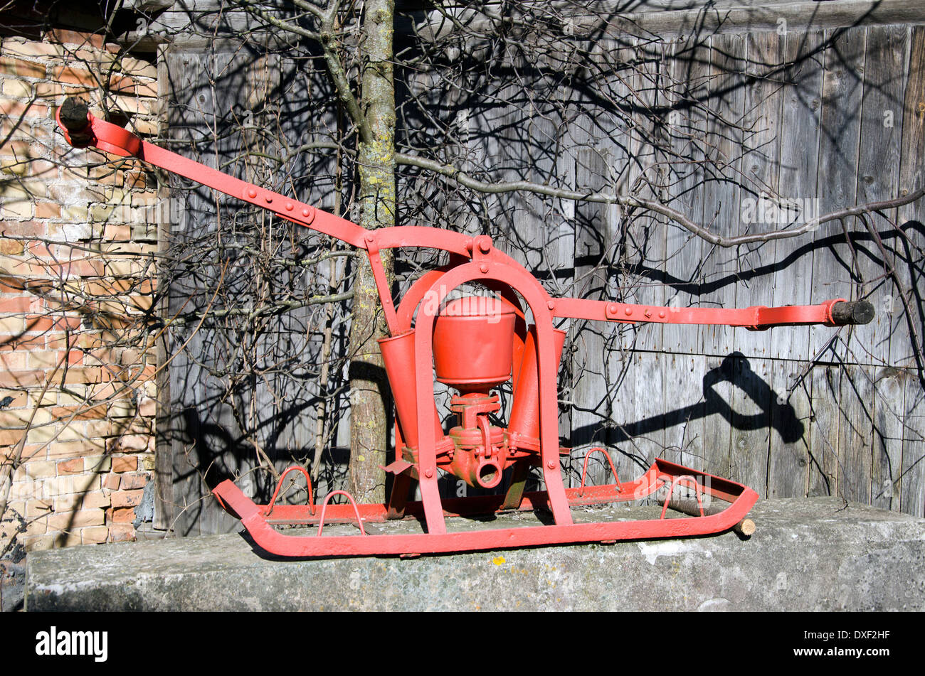 vintage historical two men red fire pump for water - Stock Image