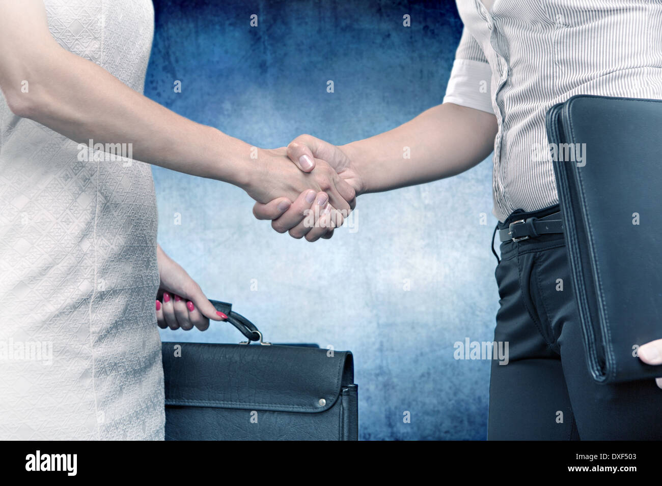 symbolic picture of two businesswomen shaking hands - Stock Image