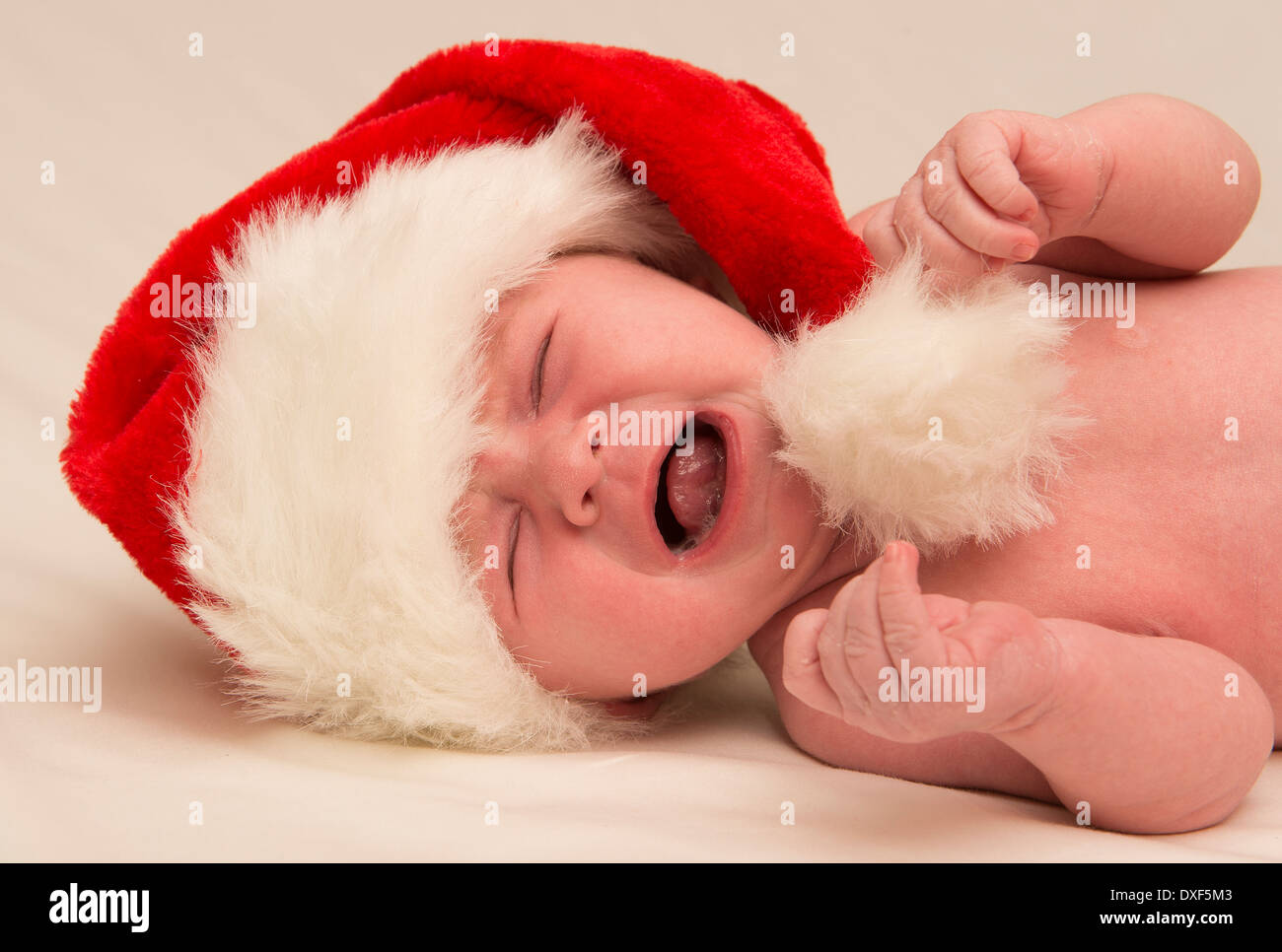Three month old crying, baby in a Santa hat Stock Photo