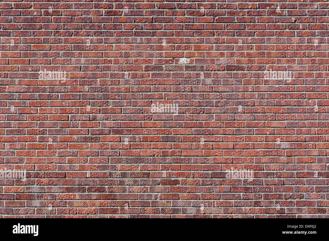 Pocked and stained red brick wall; landscape orientation. - Stock Image