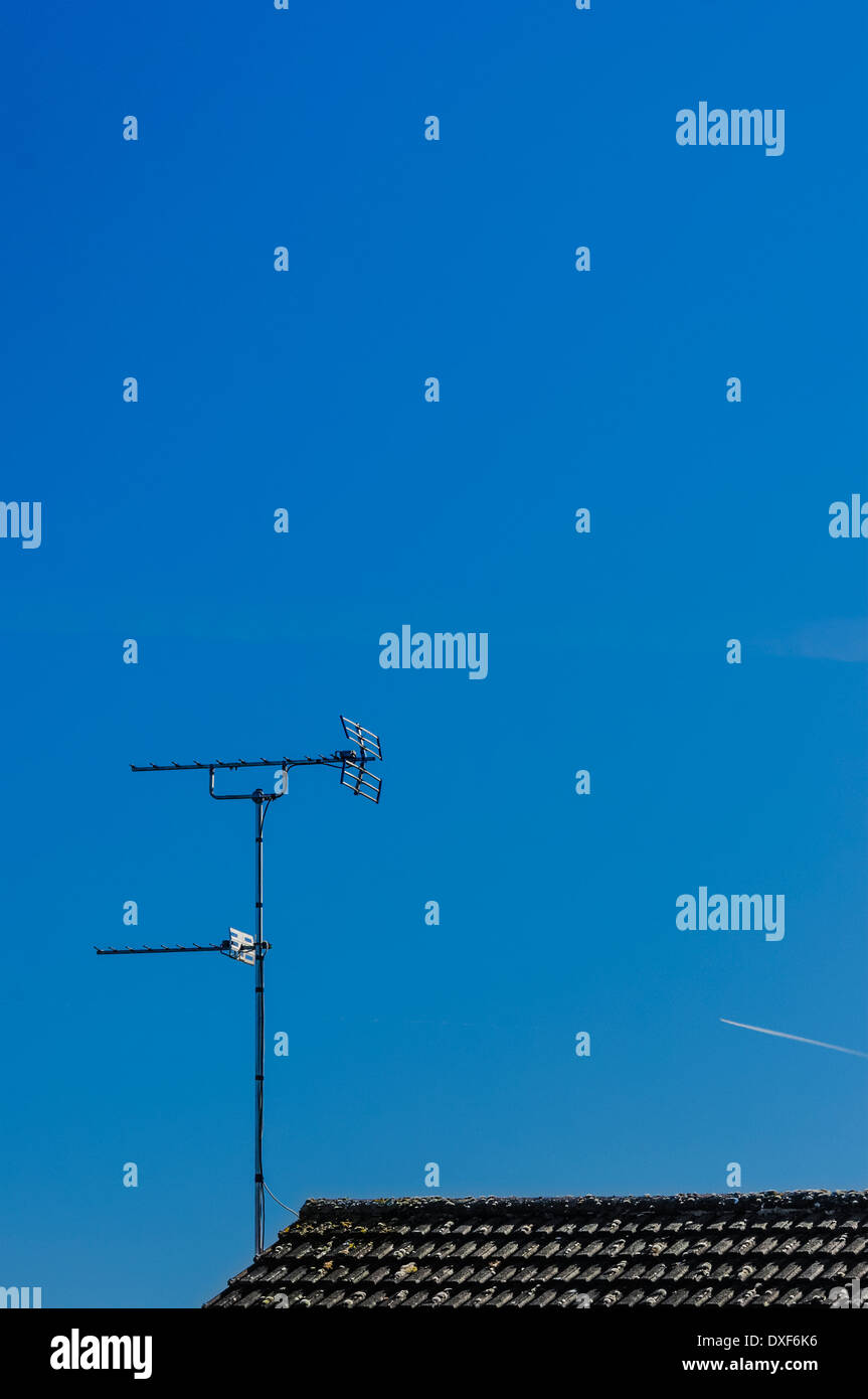 Old style TV aerial / antenna on top of black tiled roof against mainly blue sky. - Stock Image