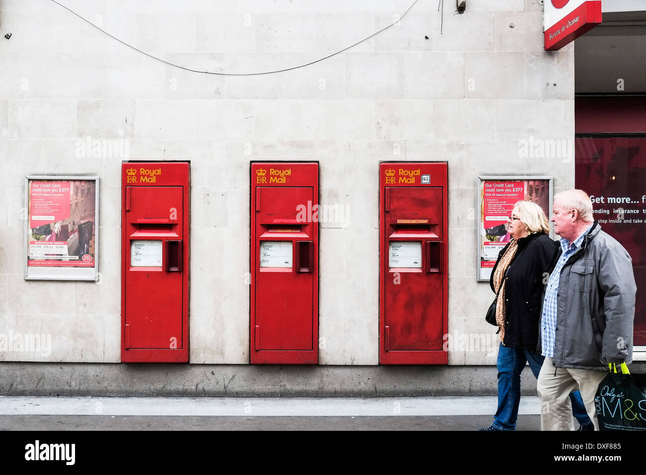 Three Royal Mail letter boxes in a wall in London. - Stock Image