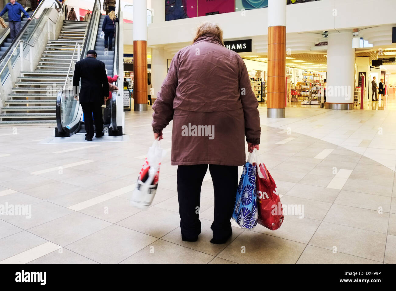 A tired elderly shopper in a shopping mall. - Stock Image