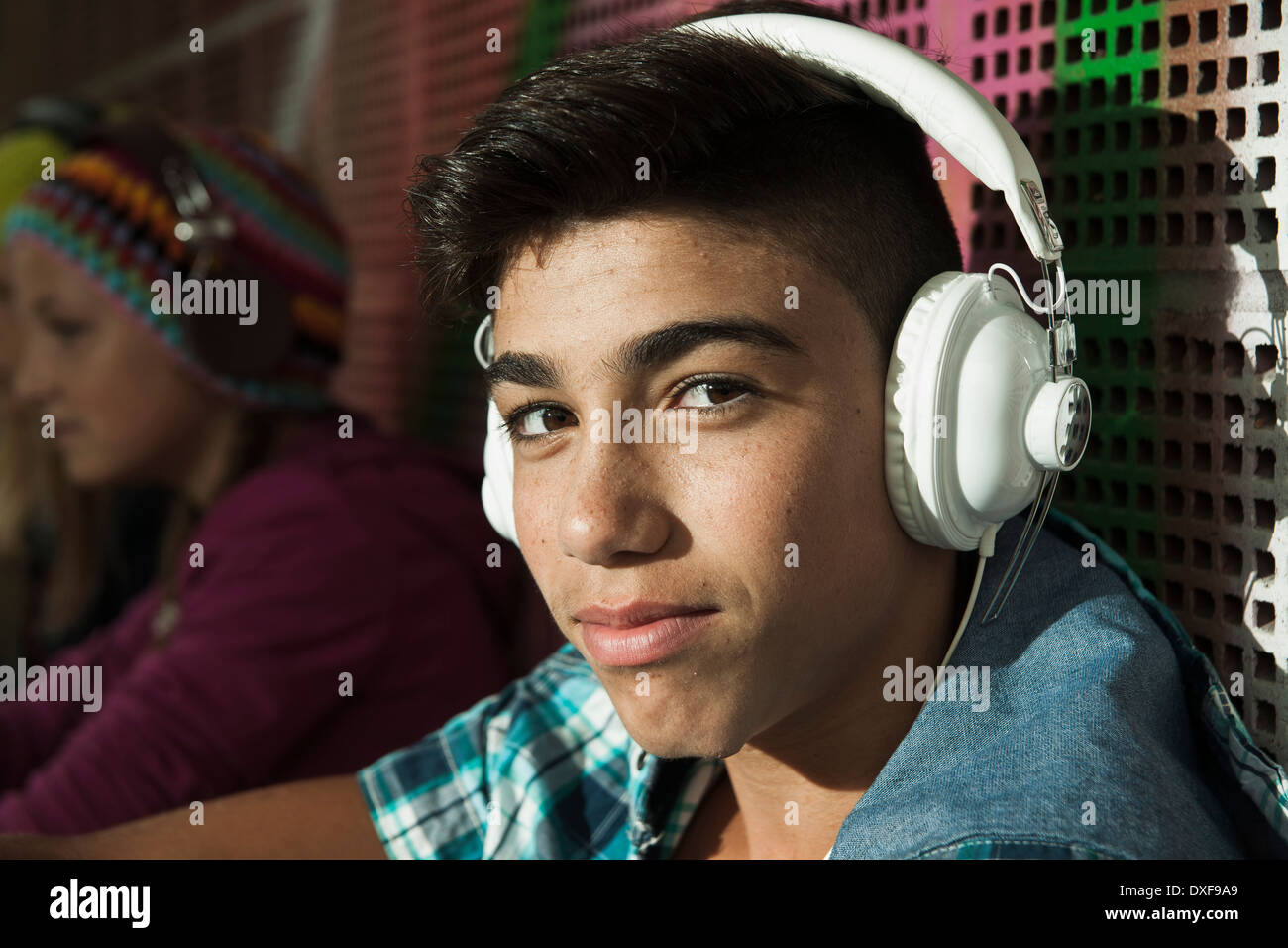 Close-up portrait of boy sitting next to wall outdoors, wearing headphones and looking at camera, Germany Stock Photo