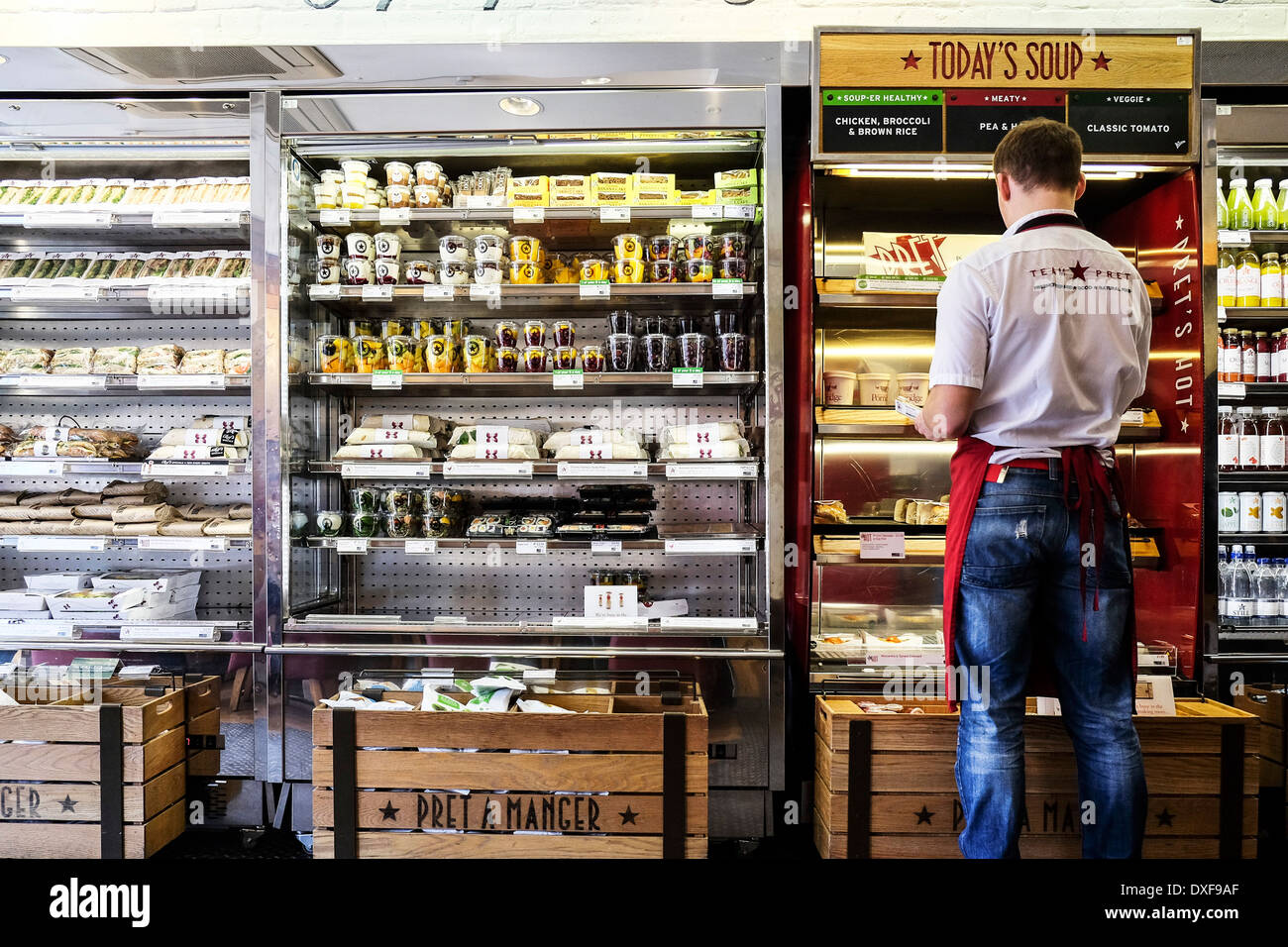 A member of the Pret a Manger staff stocking shelves. - Stock Image