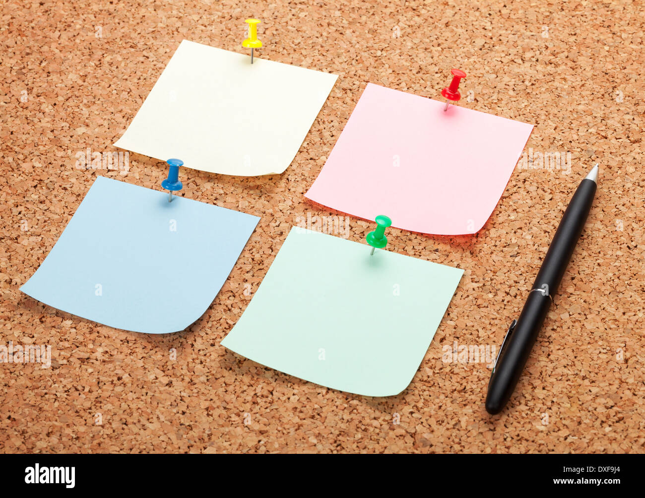 Blank postit notes on cork notice board with pen - Stock Image