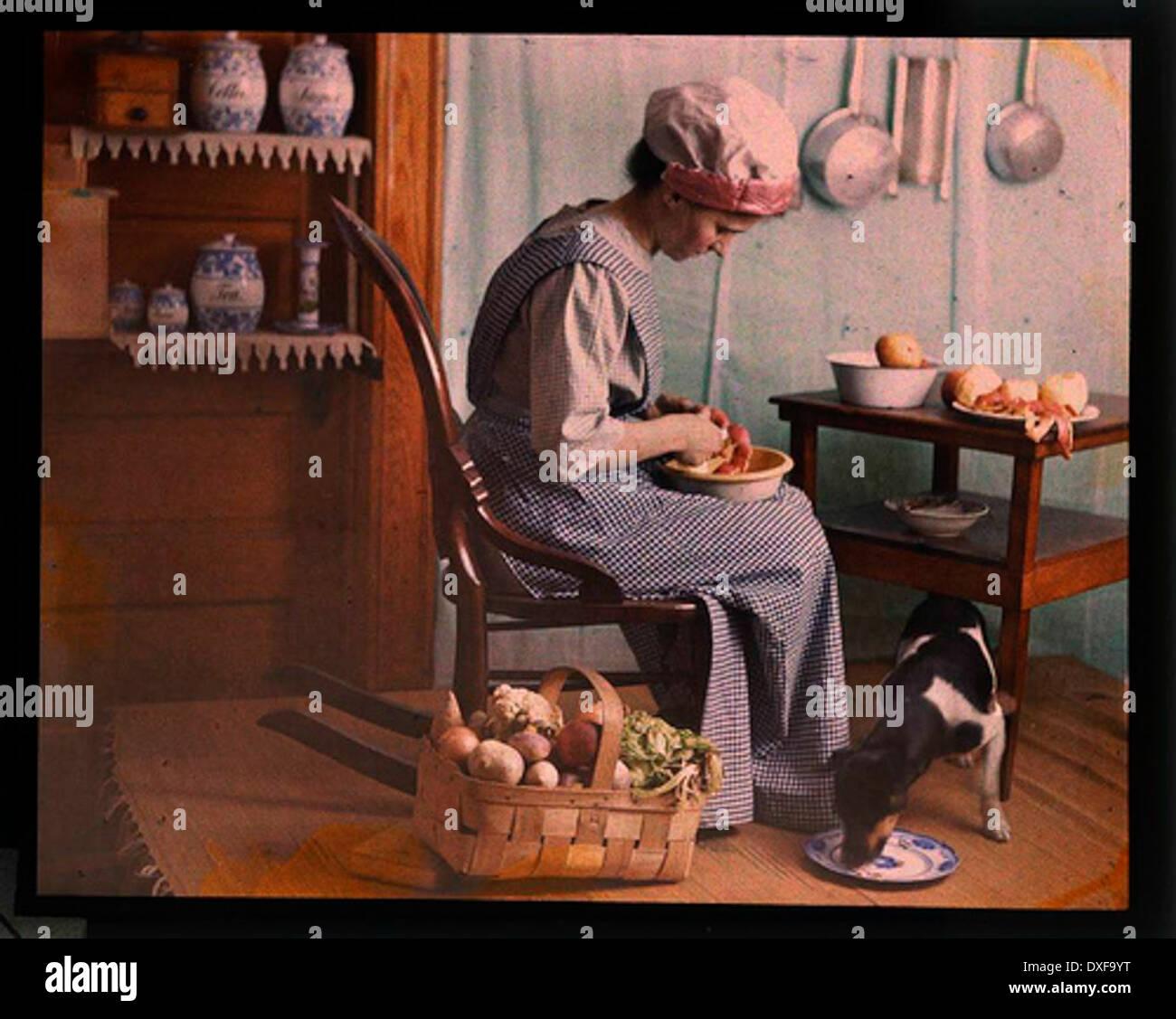 Genre scene, woman in kitchen peeling vegetables - Stock Image