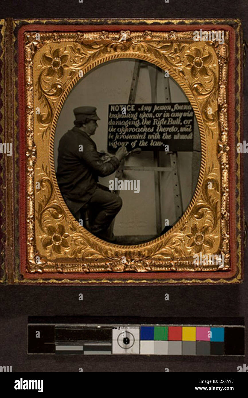 Man lettering a sign on an easel Man lettering a sign on an easel - Stock Image