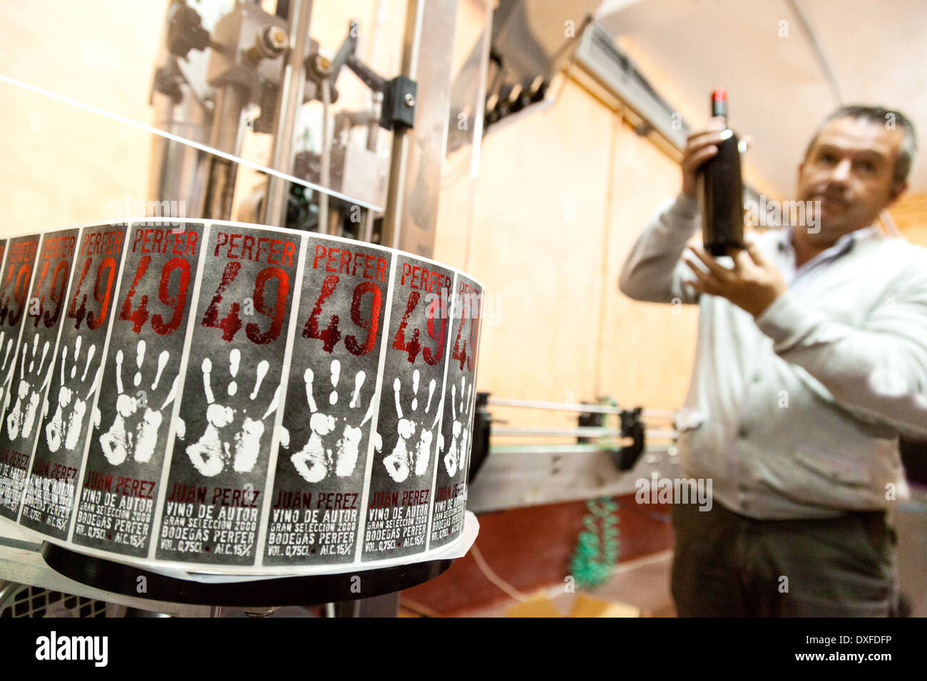 The owner of the Perfer Winery vineyard bodega, and his bottle labelling machine, Almeria, Andalusia Spain Europe - Stock Image