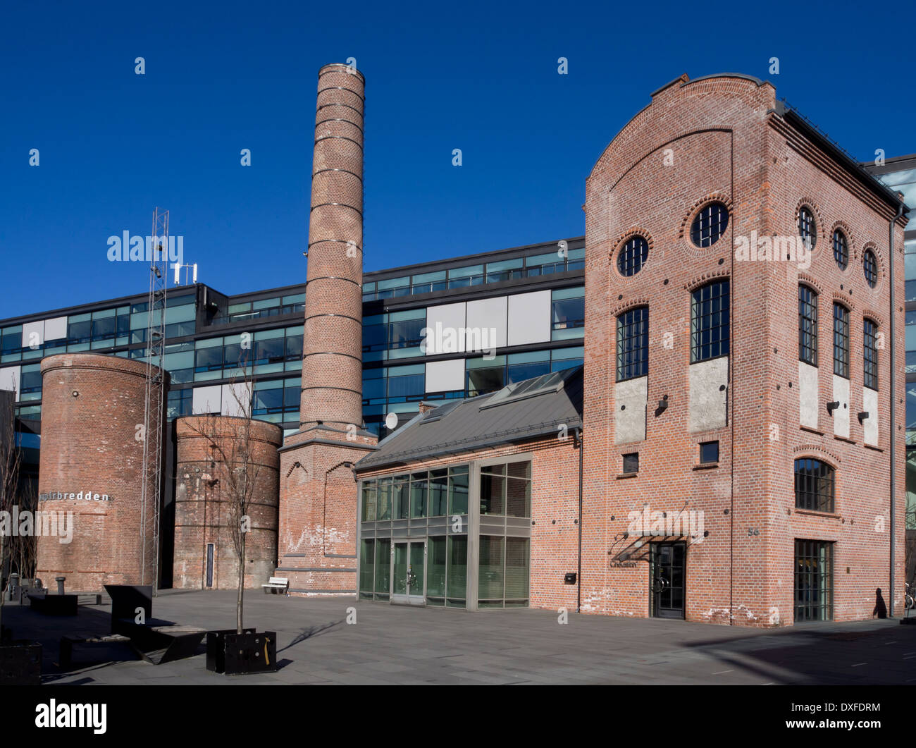 Red brick buildings and chimney from old papermill integrated in modern urban architecture Drammen Norway - Stock Image
