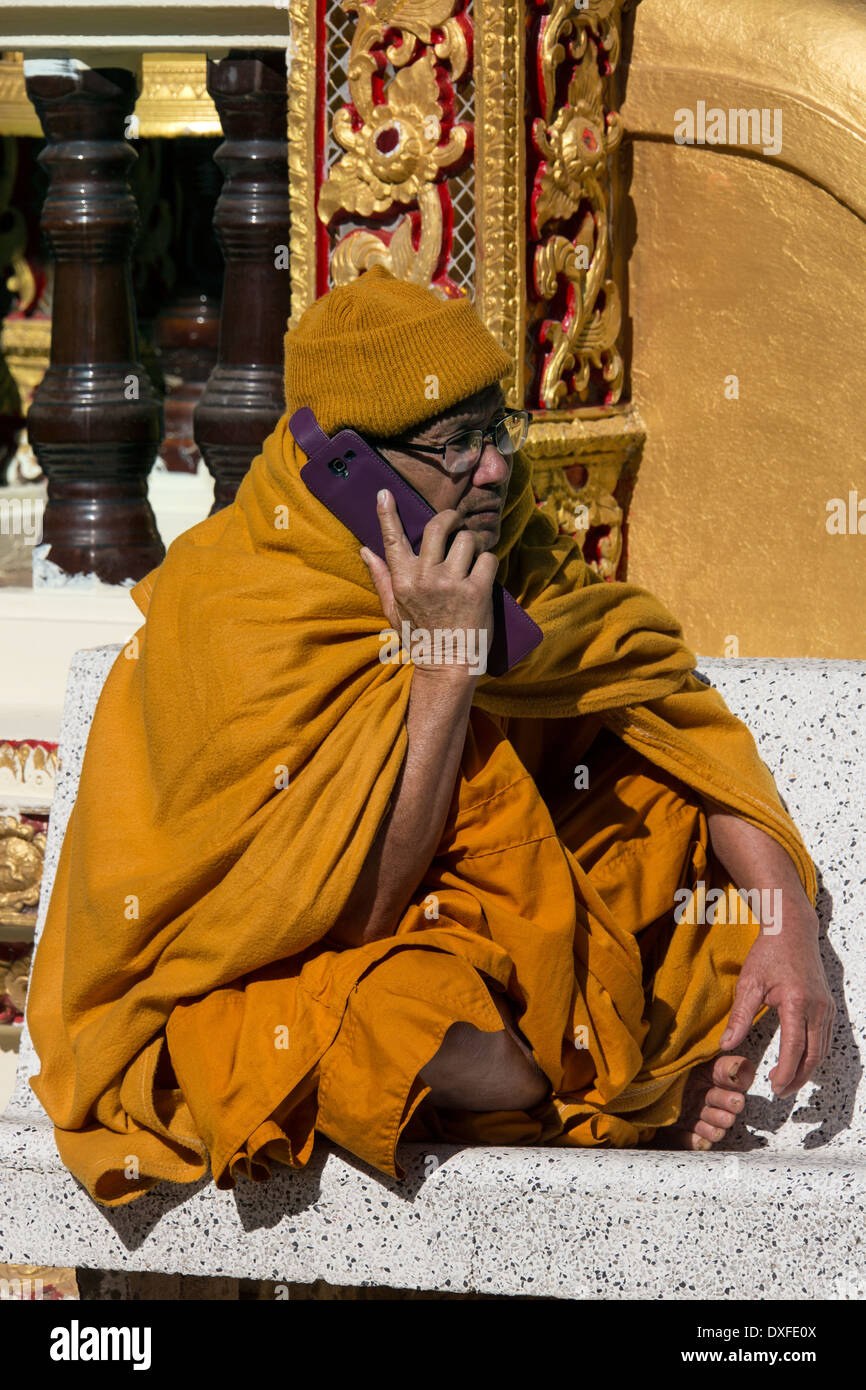 A Thai monk using a cellphone at Doi Suthep Buddhist Temple near Chiang Mai in northern Thailand. - Stock Image
