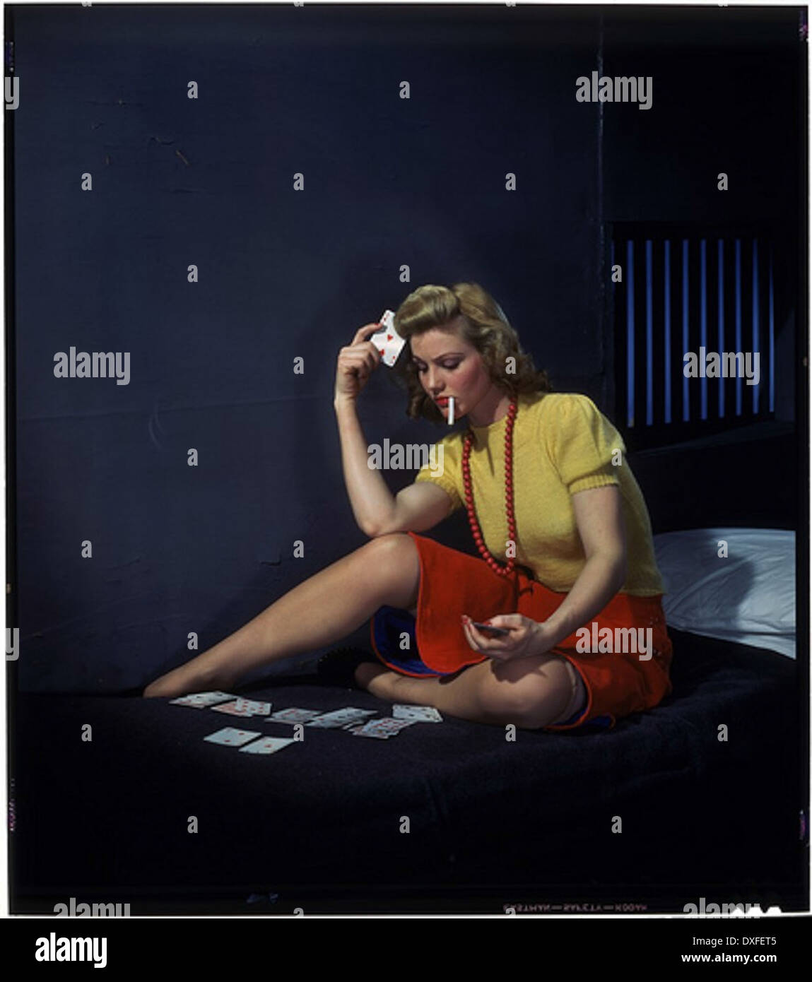 Woman in cell, playing solitaire - Stock Image