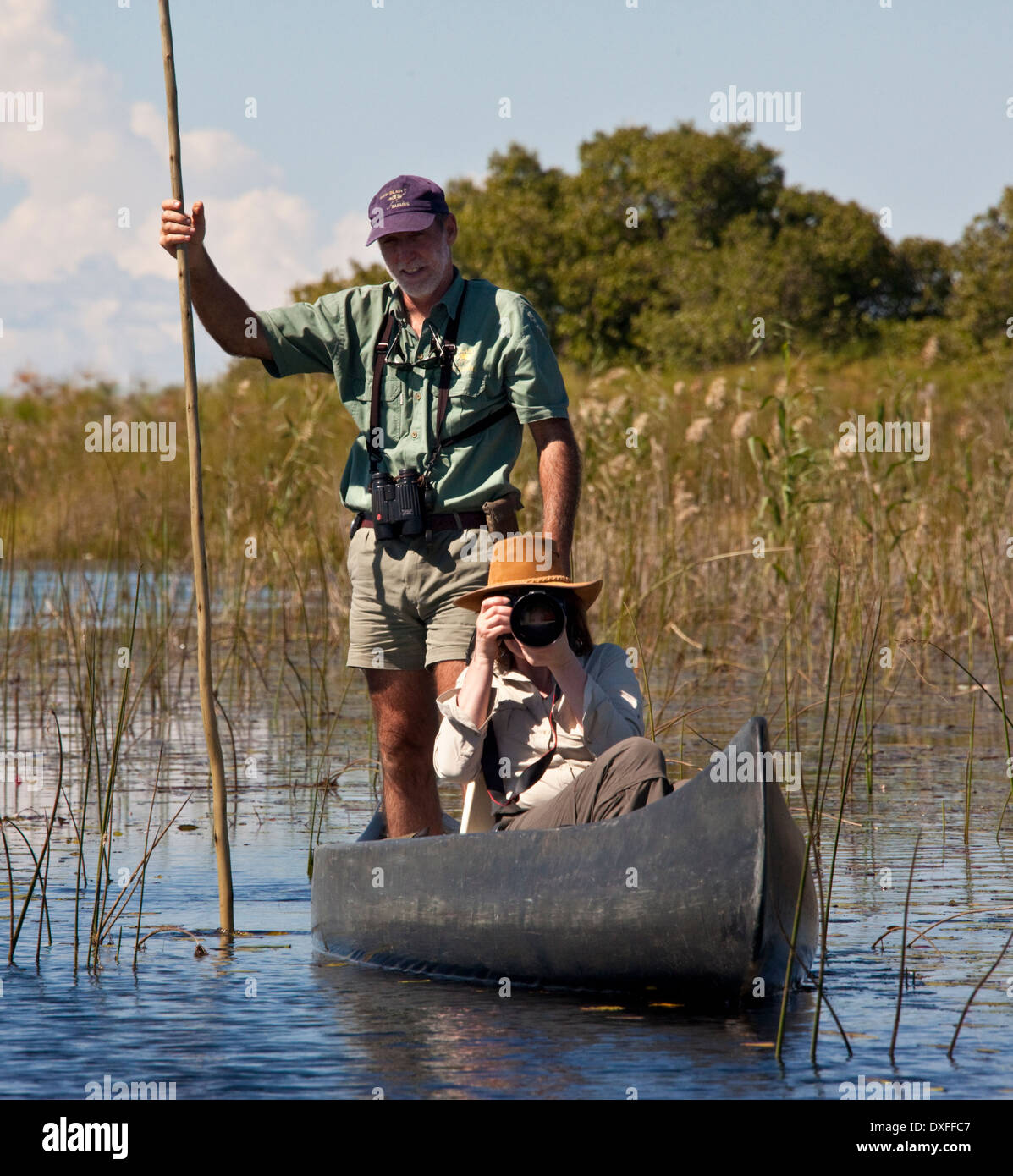 Tourist and guide in the Okavango Delta in Botswana. - Stock Image