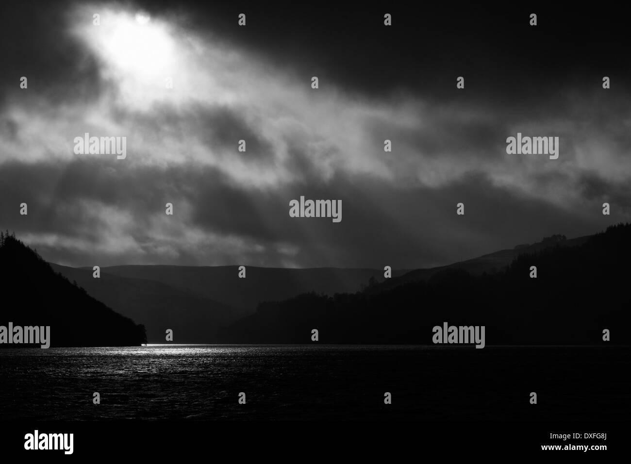 Sun breaks through cloud over Caban Coch dam. - Stock Image