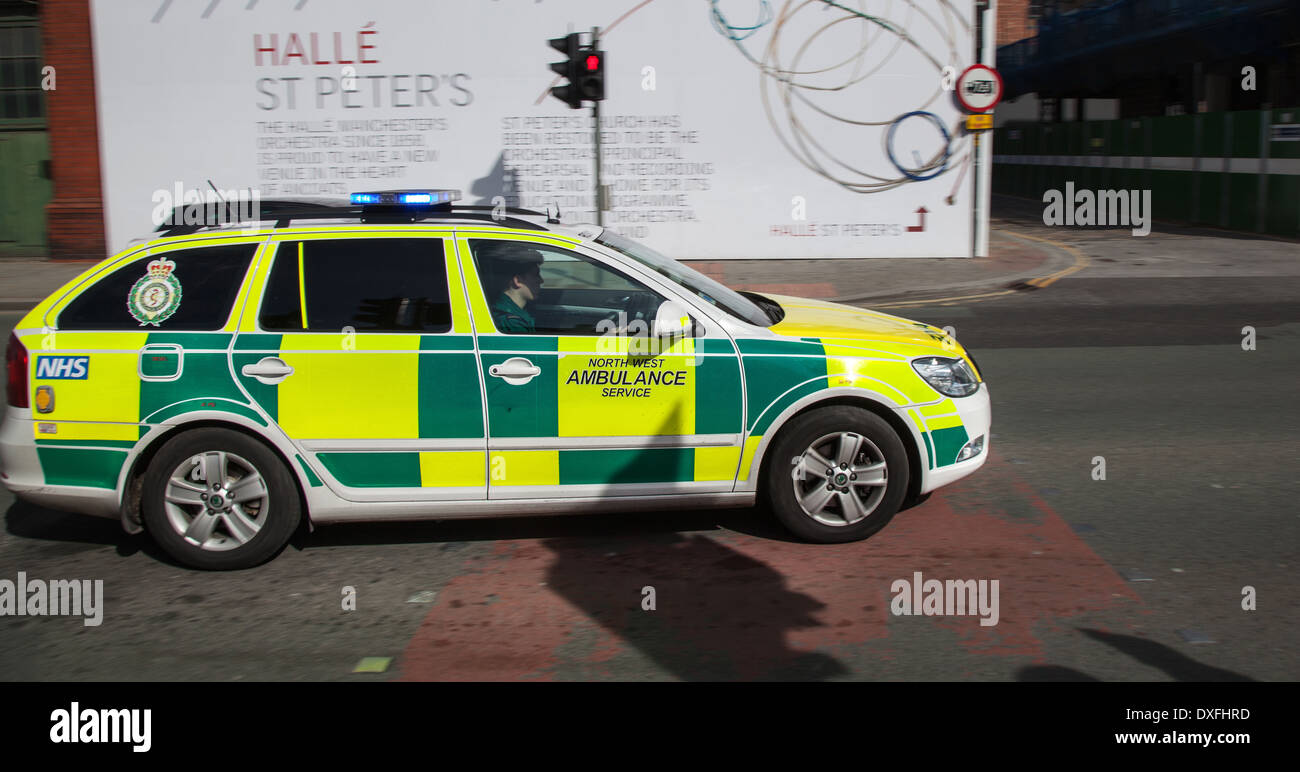 999 Emergency responder car _ NHS North West ambulance speeding through Ancoats in Manchester, UK - Stock Image