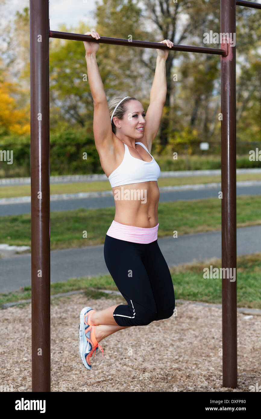 Portrait View of a Fit Woman Performing Pull Up Exercise Outdoors in a Park - Stock Image