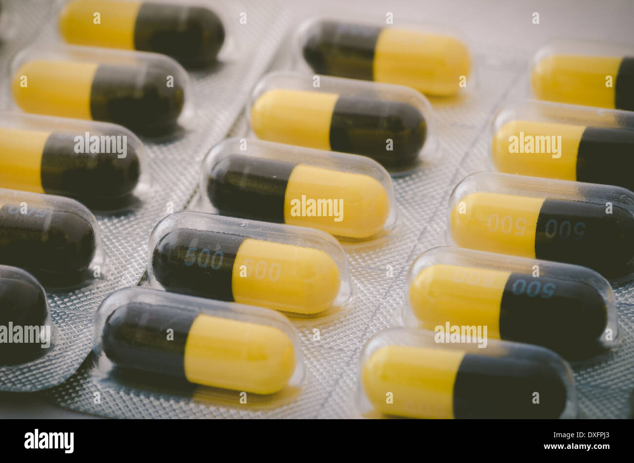 Black and yellow capsule pack medicine heath concept - Stock Image