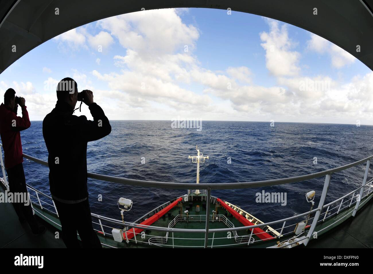 Aboard Xuelong. 26th Mar, 2014. Crew members of Chinese icebreaker Xuelong scan the sea to search for missing Malaysia Airlines Flight MH370 in the area where Chinese airborne searchers spotted some suspicious objects in the southern Indian Ocean on March 26, 2014. Credit:  Zhang Jiansong/Xinhua/Alamy Live News - Stock Image