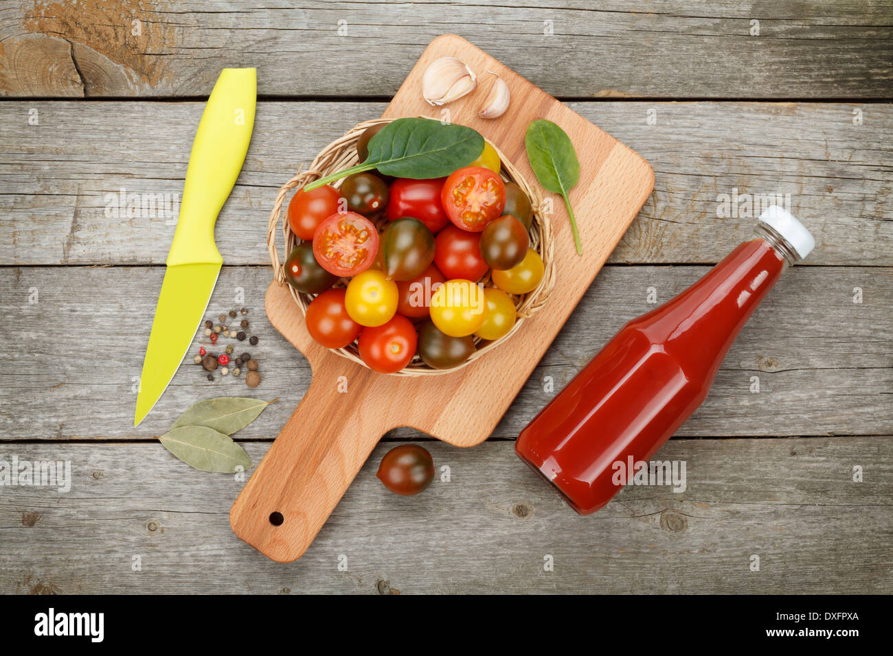 Cherry tomatoes on cutting board and ketchup bottle over wooden table background - Stock Image