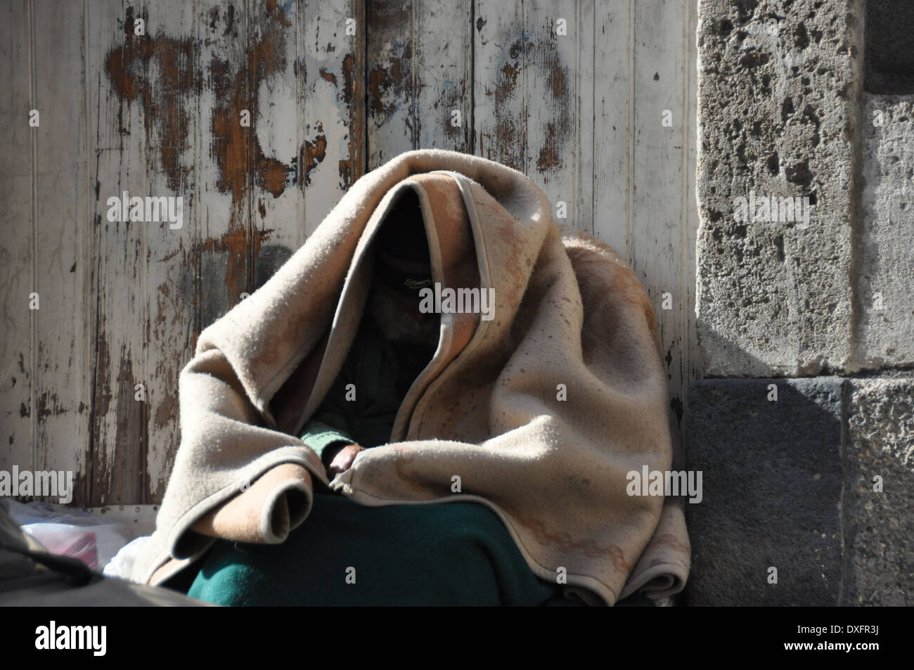 Homeless person hiding under a blanket, in Catania, Sicily, Italy - Stock Image