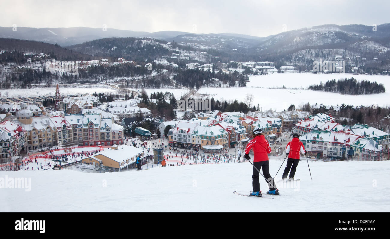 Mont-Tremblant, Canada - February 9, 2014: Skiers and snowboarders are sliding down the main slope at Mont-Tremblant. - Stock Image
