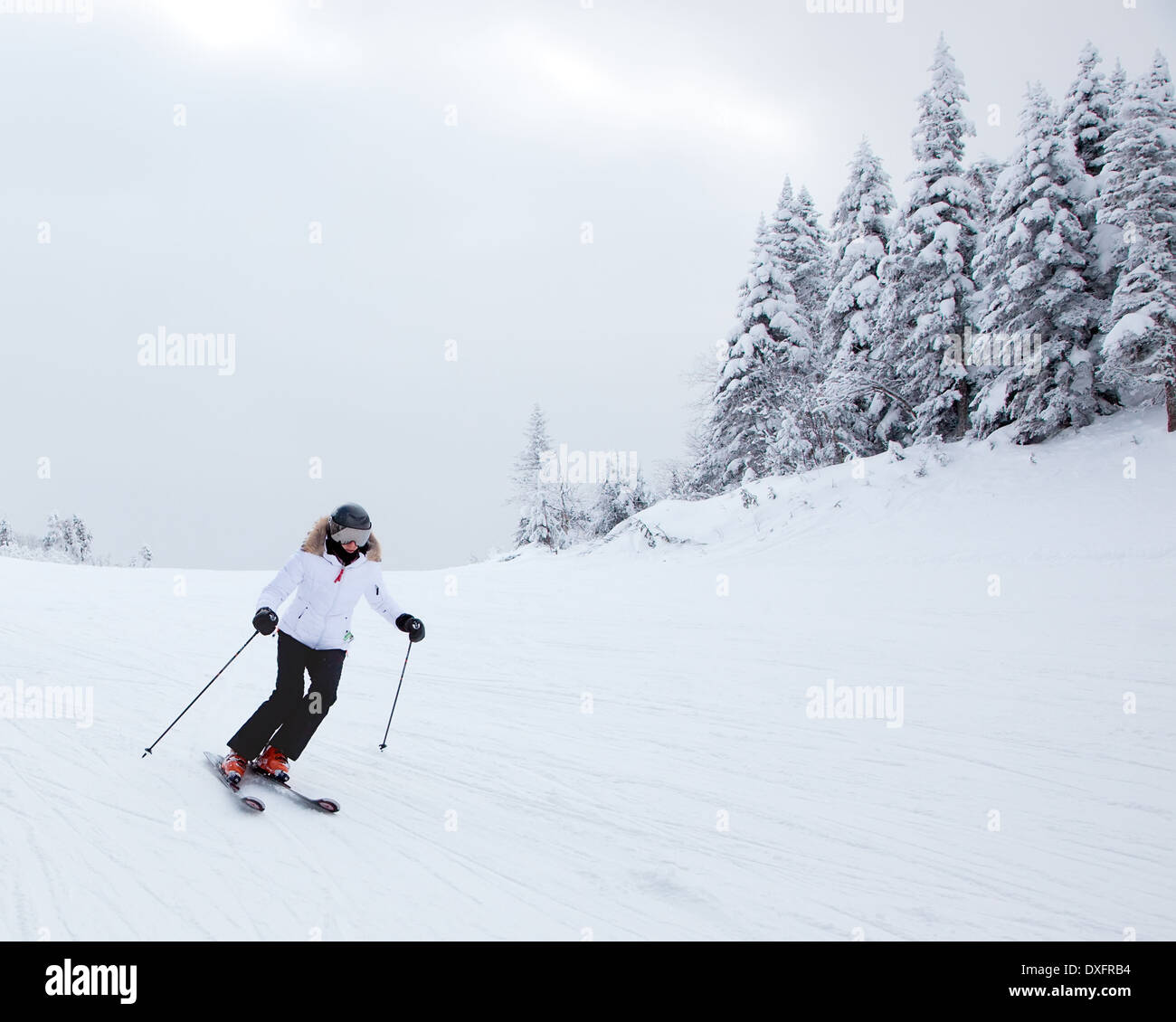 Mont-Tremblant , Quebec, Canada - February 9, 2014: A lonely skier is sliding down an easy slope at Mont-Tremblant Ski Resort. - Stock Image