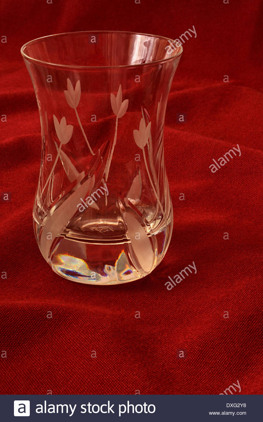 crystal cup for Arabic coffee on dark red tablecloth - Stock Image