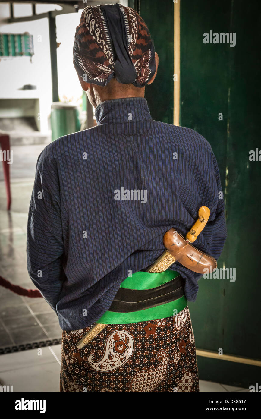 guard of the Kraton, the sultanate palace of Yogyakarta, wearing a kris at his back within his traditional sarong. - Stock Image