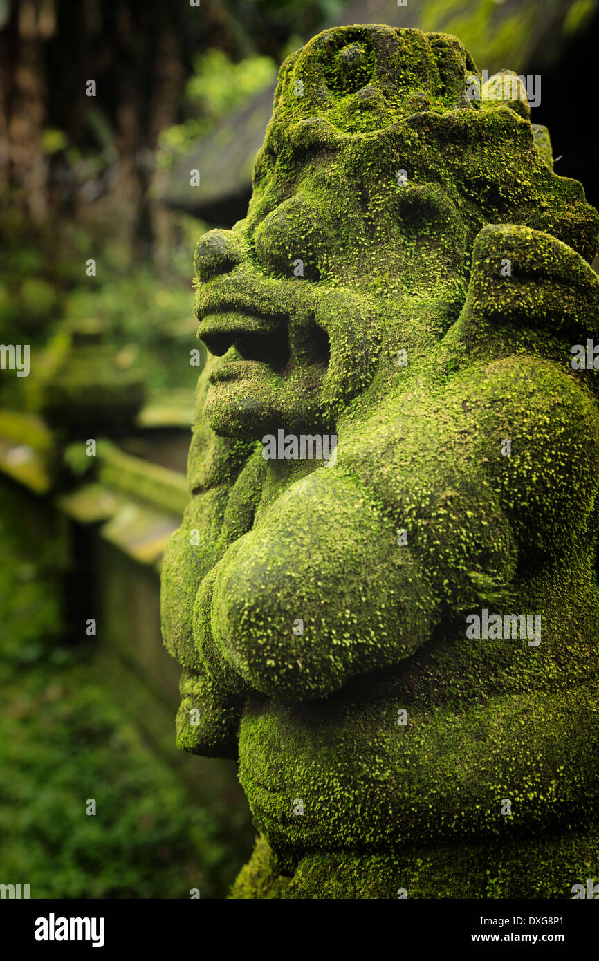 Moss covered statue of a guard in the Pura Luhur Batukau complex, central Bali, Indonesia. - Stock Image
