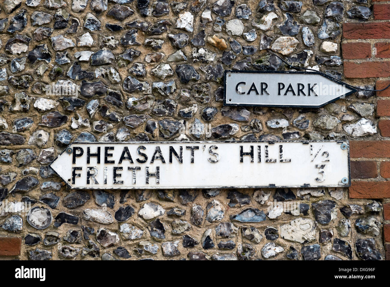 Old road & car park sign on the wall of a brick and flint built walled house Hambleden village Bucks UK - Stock Image