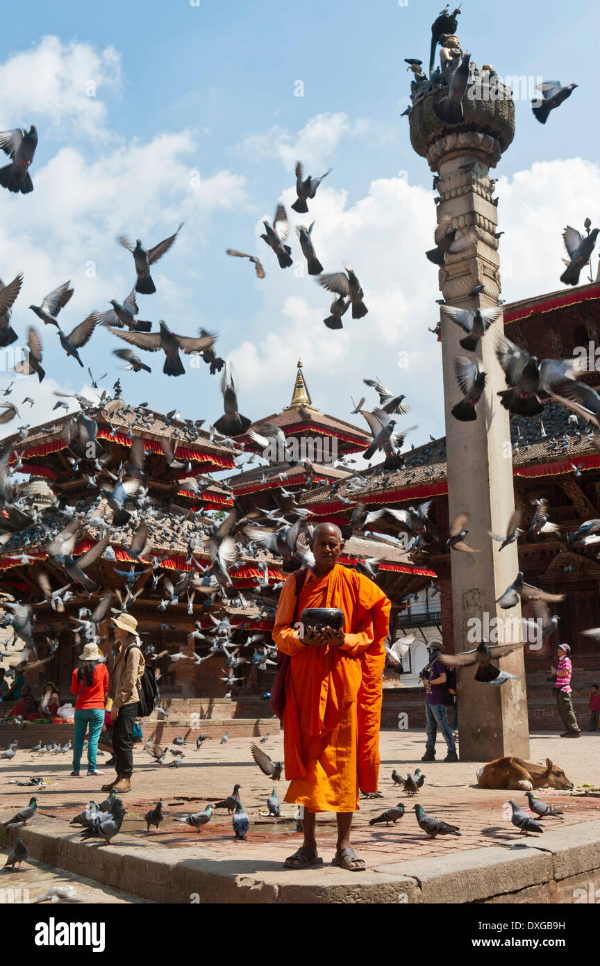 Buddhist monk with a begging bowl standing in front of Hindu temples, many pigeons flying up, pagoda, square outside the Hanuman - Stock Image