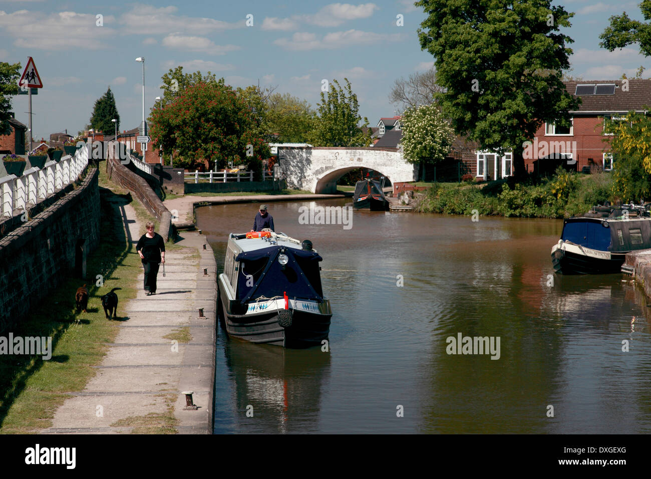 A narrowboat about to enter Kings Lock on the Trent and Mersey Canal at Middlewich - Stock Image