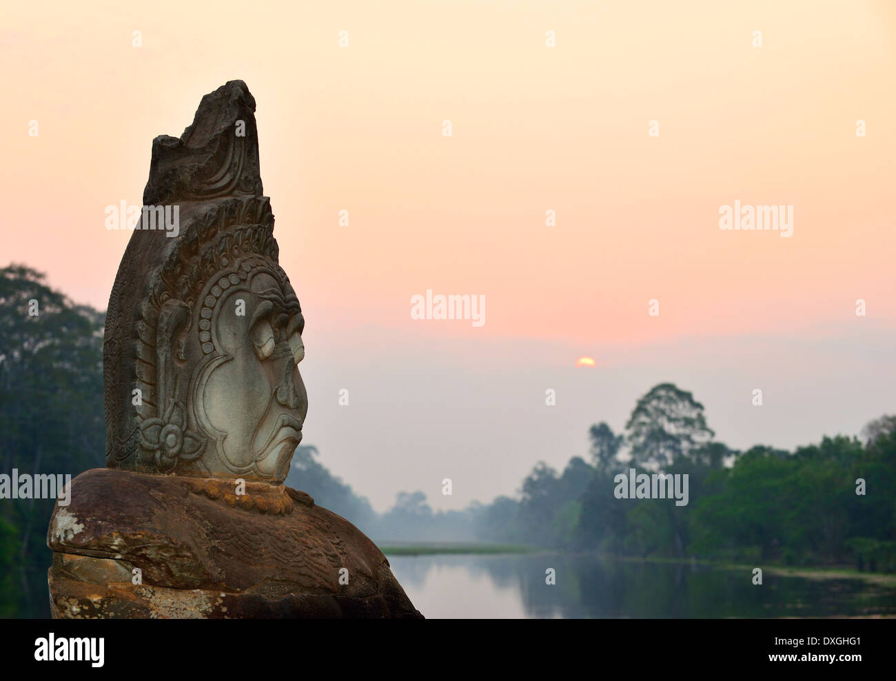 Sunrise over  water  and in between row of gods on path to  Angkor Thorn ,south gate  Siem Reap , Cambodia - Stock Image