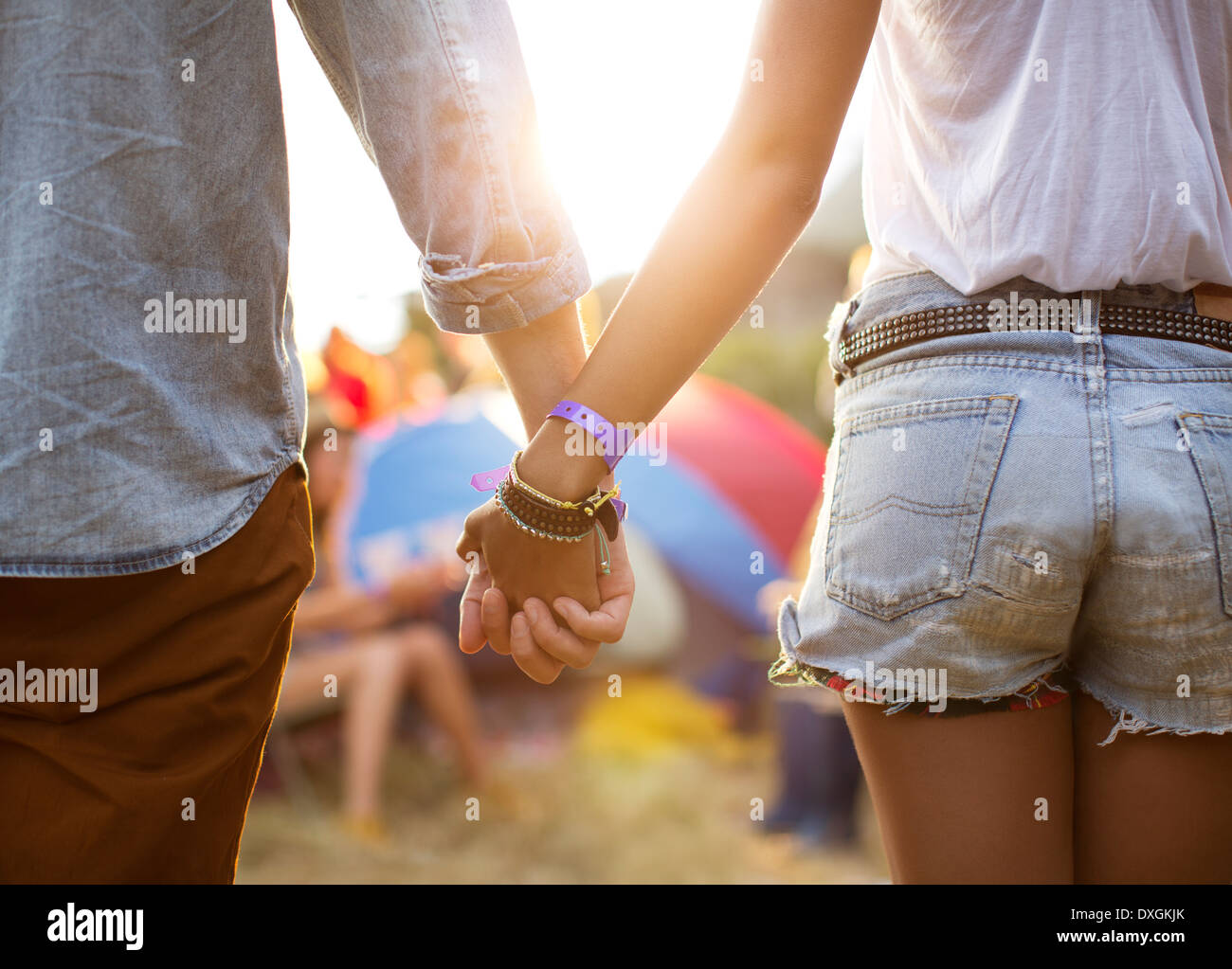 Couple holding hands near tents at music festival - Stock Image