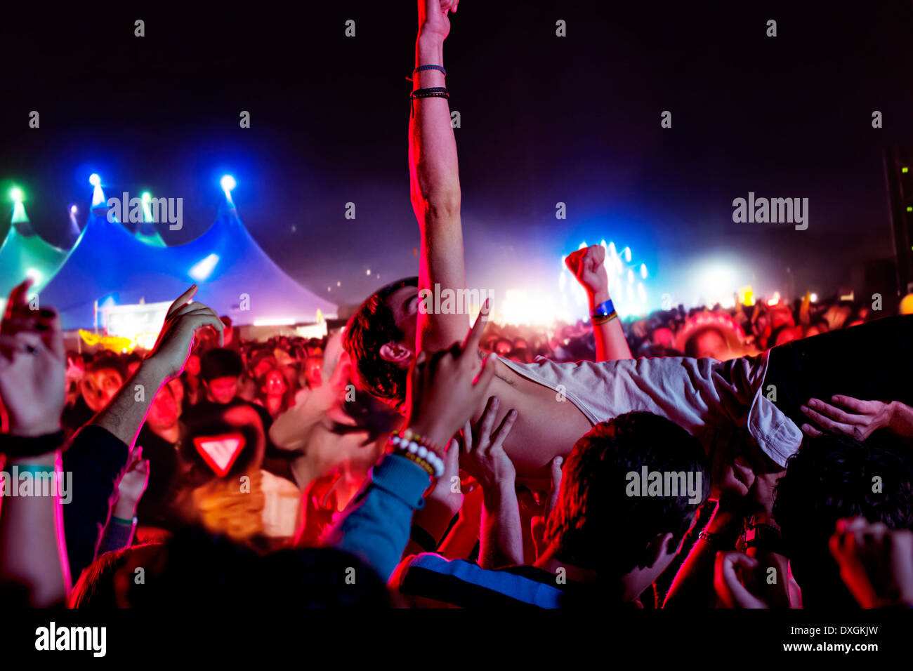 Man crowd surfing at music festival - Stock Image